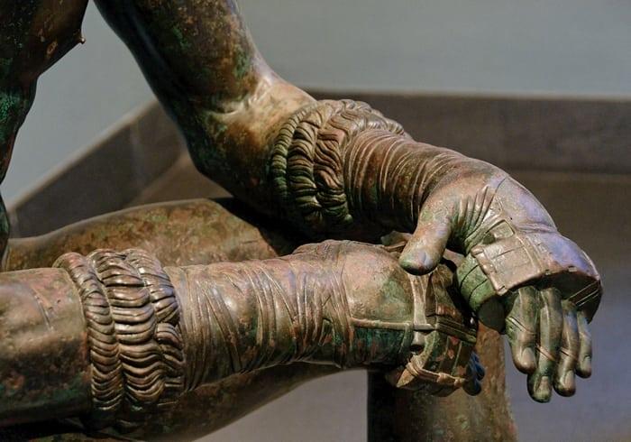 античная статуя с ремнями на рукках